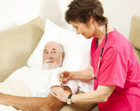 Home Nursing - Getting a Shot. Home health nurse giving a shot to an elderly patient Royalty Free Stock Photography