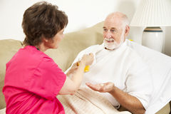 Home Nursing - Take Medicine. Home health nurse giving an elderly patient juice to make his medicine go down Stock Photography