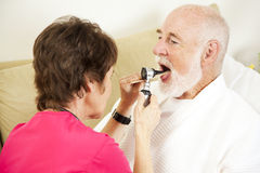 Home Nursing - Throat Check. Home health nurse checks a patient's throat with an otoscope Stock Image