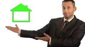 home nytt En affärsman och ett grönt miniatyrhus lager videofilmer