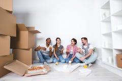 home nytt Vänner som sitter på golvet i den nya lägenheten och äter pizza, når uppackning Royaltyfria Bilder