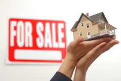 Home offerred for sale. Female real estate agent's hands offering a home for sale Stock Photo