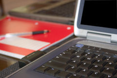 Home Office. Shared workspace in home office occupied by two laptops with red notebook.  Foreground focus Royalty Free Stock Photos