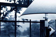 Home Office. Lamp  on desk in front of window at dusk Stock Photo