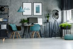 Home office with blue lamp. Blue chair, pouf and designer lamp in stylish home office with posters on concrete wall Royalty Free Stock Photography
