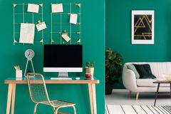Home office with computer. Study space and home office with computer on a wooden desk in a modern living room interior with green walls stock photo