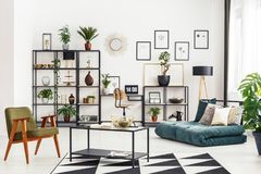 Home office corner. With desk and laptop in white living room interior with folded mattress sofa, fresh plants and metal rack royalty free stock image