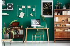 Home office corner. Home office and study corner with wooden desk and computer in green room interior with plants and poster stock photo