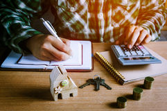 Home office desk.business concept background. Selective focus wood home key and step up gold coin or currency on wooden table with document.Blur hand man royalty free stock images