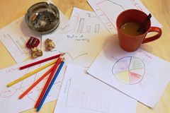 Home office. Desk with charts on paper sheets with cigarette, coffee, crayons and shawings Stock Photography