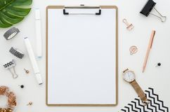 Home office desk with clip board mockup, glasses, golden stationery, green leaves and color markers for drawing. Home office desk with clip board mockup, glasses Royalty Free Stock Photos