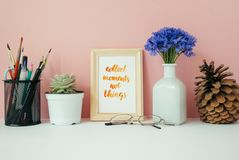 Home office desk in front of pink pastel background. Card with quote stock image