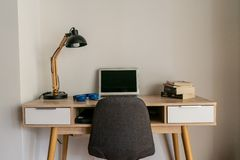 Home office desk with laptop and books stock photography