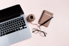 Home office desk with laptop, kraft notepad, glasses, calligraphy pen, twine rope stock image