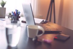 Home office. Detail of a desk with a laptop, smart phone and planner in a home office. Selective focus on the keyboard stock images