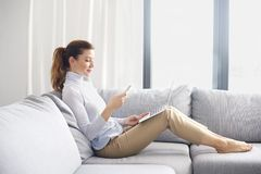 Managing her business from home. Home office. Full length shot of an attracitve woman using mobile phone and laptop while working from home Royalty Free Stock Images