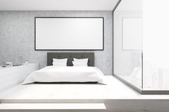 Home office with a glass wall in a bedroom. Front view of a home office in a bedroom. There is a bed with a table to the left of it and a framed horizontal Royalty Free Stock Photos