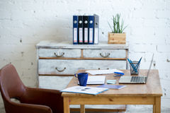 Home office interior. In loft space with white brick walls. Cozy workplace with wooden table, office supplies, documents, notebook and laptop, leather chair and stock image