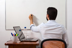 Home office, man writing in white board Royalty Free Stock Photo