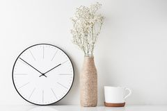 Home office minimal workspace desk with wall clock. Front view desk with round wall clock, cup and flower in bottle vase on white background. Home office minimal royalty free stock photos