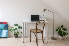 Home office. Vintage chair at white desk with laptop computer. stock image