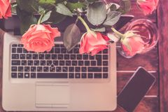 Home office work space. Top view, home office work space. Workplace with laptop, roses, phone on wooden background Royalty Free Stock Image
