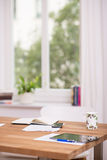 Home office or work station. With various electronic devices and paperwork spread out on a table in front of a window Royalty Free Stock Photos