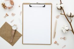 Home office workspace mockup with envelope, clip board,cotton flowers and golden accessories. Flat lay, top view. Mock up Stock Photo