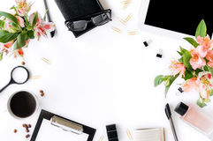 Home office workspace with tablet, clipboard, accessories, coffe. Home office workspace with tablet, clipboard, accessories. cup of coffee and bouquet of flowers Stock Image