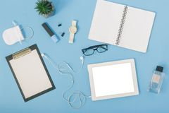 Home office workspace tablet, notebook, spectacles, clipboard, h. Home office workspace with  tablet, notebook, perfumes, spectacles, clipboard, headphones Stock Photos