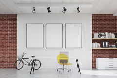 Home office with yellow chair and three posters Royalty Free Stock Images