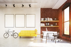Home office with yellow sofa and three posters Stock Image