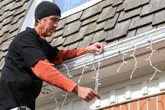 Home owner  hanging exterior Christmas lights Stock Photography