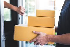 Home owner open door to delivery man standing with parcels in hands outdoors, Home delivery service and working with service mind royalty free stock image