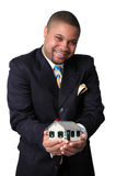 Home Ownership. African American businessman holding a house representing home ownership Stock Image