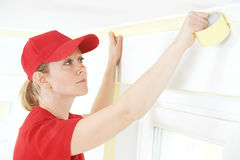 Home Painter with masking tape. Woman painter worker protecting ceiling moulding with masking tape before painting at home improvement work Royalty Free Stock Photography