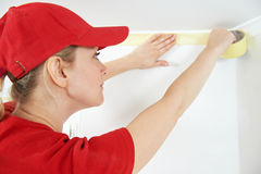 Home Painter with masking tape. Woman painter worker protecting ceiling moulding with masking tape before painting at home improvement work Stock Images