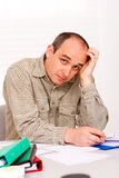 Home paperwork. An adult businessman / student working at home with a thinking expression looking at the camera Stock Photos