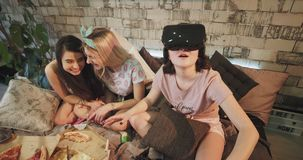 At home party ladies in pajamas spending a good time together one of the girl using a VR exploring the new technology stock video