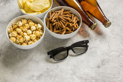 Home party with TV watching, snacks and beer on stone background. Home party with TV watching, snacks, pop corn, chips and bread crumbs and beer on stone Royalty Free Stock Images