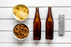 Home party with TV watching, snacks and beer on white background top view. Home party with TV watching, snacks, chips and bread crumbs and beer on white Royalty Free Stock Photos