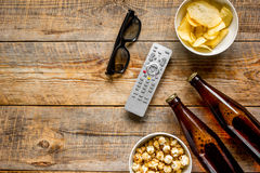 Home party with TV watching, snacks and beer on wooden background top view mock up. Home party with TV watching, snacks, pop corn, chips and beer on wooden Stock Photo