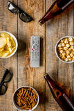 Home party with TV watching, snacks and beer on wooden background top view. Home party with TV watching, snacks, pop corn, chips and bread crumbs and beer on Royalty Free Stock Image