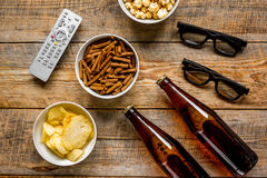 Home party with TV watching, snacks and beer on wooden background top view. Home party with TV watching, snacks, pop corn, chips and bread crumbs and beer on Royalty Free Stock Photo