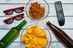 Home party for two persons. Cinema or television watching concept with two sorts of beer in bottles and salted snacks Stock Images