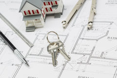 Home, Pencil, Ruler, Compass and Key Resting on House Plans Royalty Free Stock Images