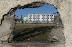 Home of people and football field who can see through the hole of a concrete fence Stock Images