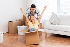 Happy couple having fun with boxes at new home. Home, people, moving and real estate concept - happy couple having fun and riding in cardboard box at new home royalty free stock photography