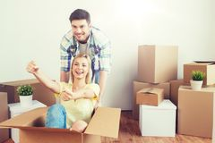 Happy couple having fun with boxes at new home Royalty Free Stock Photography