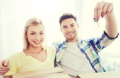 Happy couple with key and boxes moving to new home Royalty Free Stock Image
